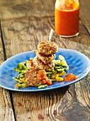Chicken and sesame seed meatballs on a bed of vegetables with sweet chilli sauce