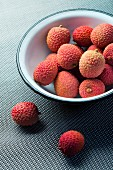 A bowl of unpeeled lychees