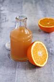 A bottle of apple juice and a halved orange