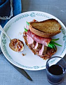 A roast beef sandwich with grilled bread, beans and onion relish