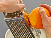 An orange being grated