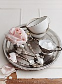 Teacups, a sugar pot, spoons and a rose on a silver tray