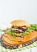 A cheeseburger with rocket on a wooden platter