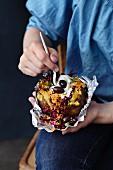 A man eating a kumpir (Turkish jacket potato) with couscous