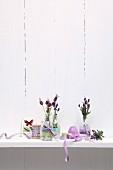 Lavendelzweige in Glasflaschen mit Masking Tape und Schleifenbänder dekoriert, auf Ablage vor geweisselter Holzwand
