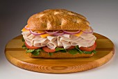 Turkey ham, cheese, onions and tomatoes on a ciabatta roll