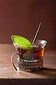 A glass of black tea with a sage leaf