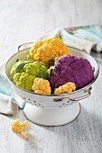 Different coloured cauliflower in a colander