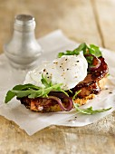 A slice of bread topped with a poached egg, bacon and rocket