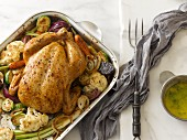 A whole roast chicken in a roasting tin surrounded by cauliflower, carrots, Brussels sprouts and onions with herb butter on the side