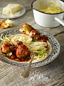 Spaghetti with meatballs served with bread and grated cheese