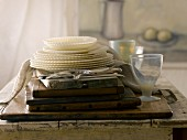 A stack of vintage plates, glassware and cutlery in front of a painting and a curtain
