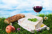 An arrangement of cheese featuring a glass of red wine and an apple