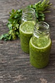 Green smoothies on a wooden table with a bunch of parsley in the background