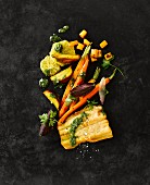 Wallerfilet mit roter Bete, gelber Bete, Möhren, Kräutern, Orangen und Pesto
