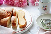 Sweet yeast bread on a rustic ceramic platter with a coffee cup, cake tones, a napkin, tablecloth and peonies