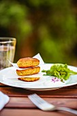 Salmon cakes with salad and borage flowers on a garden table
