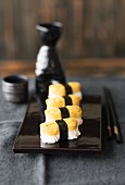 Tamago nigiri sushi on a black varnished platter