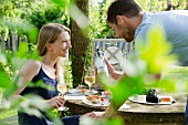 A couple drinking white wine with a picnic in a garden