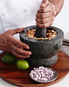 Ingredients for curry being crushed in a mortar