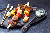 Lamb and bread skewers on a hot stone