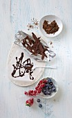 Grated chocolate, flaked chocolate, chocolate glaze and sugared berries