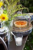 Aprikosentarte auf Korbteller mit Glashaube, Kaffeekanne und französisches Landhausgeschirr mit Wiesenstrauss auf Eisenregal