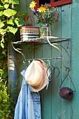 Vintage Aussengarderobe mit Sommerstrauss auf der Ablage, Sonnenhut und Gartenutensilien an Haken