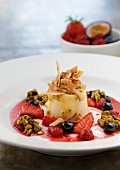 Passion fruits ice cream with berry sauce, pistachios and grated coconut