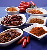Spices in white dishes and chilli peppers on a blue surface