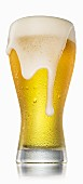 Volles Glas Bier mit Wassertropfen und überlaufendem Schaum