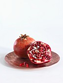 A whole and a halved pomegranate on a copper plate