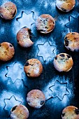 Mince pies dusted with icing sugar on a blue starry background
