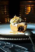 Mince Pie mit Sahne und Orangenschale, angebissen