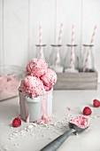 Frozen Himbeerjoghurt mit weissen Schokoladenspänen im Topf, dahinter kleine Milchflaschen