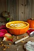 Herbstliche Kürbissuppe in ausgehöhltem Kürbis mit Sauerrahm und Kürbiskernen