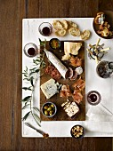 A selection of cold cuts with cheese, Prosciutto, olives, bread, almonds, jam and red wine