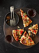 Pizza slices with peperoni, mushroom and pepper served with red wine