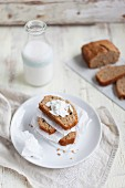 Banana bread with coconut flakes in front of a bottle of milk