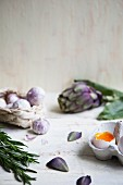 An open soft-boiled egg with field garlic, artichokes and a sprig of rosemary