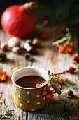 Hot chocolate in a spotted cup on a wooden table with autumnal decoration