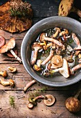Fresh forest mushrooms in an old bowl of water on a wooden table