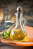 A carafe of olive oil and a sprig of green olives
