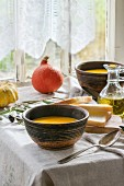 Lunch with pumpkin soup and green olives, served on an old wooden table by a window