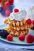 A stack of three fresh waffles topped with whipped cream and fresh berries