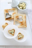 Hearts cut out of toast topped with herb butter as party food
