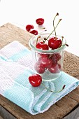 Fresh cherries with stems in a glass on a cloth on a rustic wooden board