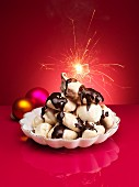 Chocolate meringues with chocolate sauce and a sparkler for Christmas
