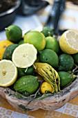 Various citrus fruits in a bowl at a market