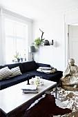 Moderner Couchtisch und dunkles Sofa, seitlich grosse Buddhafigur, auf Boden mit abblätternder Farbe